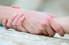 Clasped hand for help. On a granit rock Royalty Free Stock Image