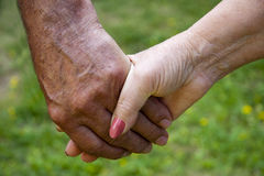 Clasped hands of adults, seniors Royalty Free Stock Photography