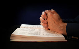 Clasped hands on a bible. While praying to God Royalty Free Stock Images