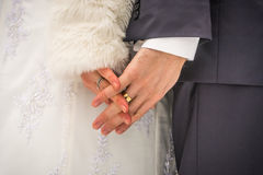 Clasped hands of the bride and groom with rings in the winter.  stock photography