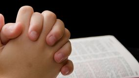 Clasped hands of a child praying over Bible stock video footage
