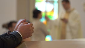 Clasped hands of man kneeling at pew in church. Clasped hands of man kneeling at the pew in the Church and praying. On the blurred background the catholic priest stock footage