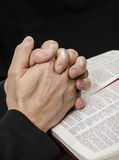 Clasped Hands in Prayer. Hands clasped over a Bible in reverent prayer Royalty Free Stock Photo