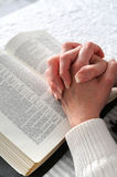 Clasped Hands in Prayer. Female hands clasped in prayer over a Bible Royalty Free Stock Images