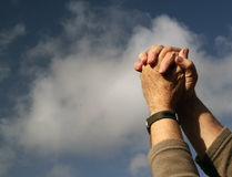 Clasped hands praying. Clouds and sky background. Clasped hands together praying. A blue sky and white cloud background Royalty Free Stock Photography