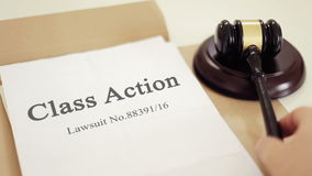 Class action folder with gavel placed on desk of judge in court stock video
