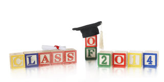 Class of 2014. A child's colorful alphabet blocks arranged to say Class of 2014.  They're topped with a tiny diploma and black cap with a white tassel.  On a Royalty Free Stock Image