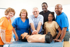 Class on CPR and First Aid. Adult education class on CPR and First Aid.  Students and teacher with dummy Stock Photography
