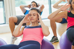 Class doing abdominal crunches on fitness balls Stock Photos