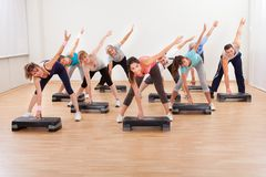 Class doing aerobics balancing on boards Royalty Free Stock Photos