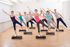 Class doing aerobics balancing on boards. Diverse group of people in a class doing aerobics balancing on boards exerting control over their muscles and breathing Royalty Free Stock Photos