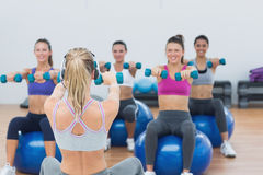 Class exercising with dumbbells on fitness balls Stock Images
