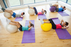 Class exercising with fitness balls at a bright gym Stock Photography