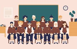 Class group portrait. Smiling girls and boys dressed in school uniform or pupils sitting in classroom against chalkboard. On background and posing for stock illustration