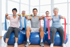 Class holding exercise belts while sitting on fitness balls Stock Photos