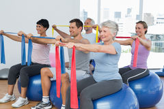 Class holding out exercise belts while sitting on fitness balls Stock Photography