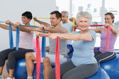Class holding out exercise belts while sitting on fitness balls Royalty Free Stock Photography