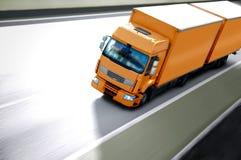 Class II. Orange semi truck on road Stock Images