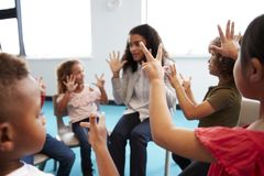 A class of infant school children sitting on chairs in a circle in the classroom, raising hands and learning to count with their f stock image
