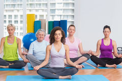 Class with instructor in lotus position at gym Stock Photo
