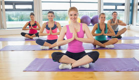 Class and instructor in Namaste position on exercise mats Stock Photo