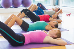Class lying on exercise mats in row at fitness studio. Side view of fitness class lying on exercise mats in row at fitness studio Stock Images