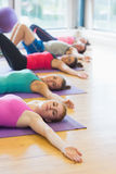 Class lying on exercise mats in row at fitness studio Stock Photos