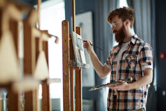 Class of painting. Adolescent guy painting during art class royalty free stock photos