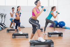 Class performing step aerobics exercise with dumbbells Royalty Free Stock Photo