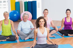 Class practicing yoga with instructor at gym Stock Photo
