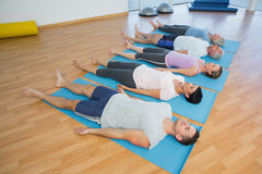 Class resting on mats in row at yoga class Royalty Free Stock Image