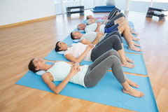 Class resting on mats in row at yoga class Royalty Free Stock Images