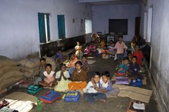 A class room. A group of students are sitting inside the primary classroom in rural India. The bag full of rice is kept inside the class room for their mid-day Royalty Free Stock Photography