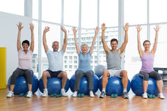 Class sitting on exercise balls and raising hands in gym Stock Photography