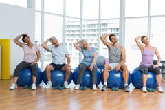 Class sitting on exercise balls and stretching neck in gym Royalty Free Stock Photos