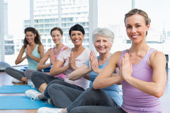 Class sitting with joined hands in row at yoga class Stock Images