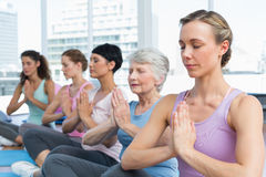Class sitting with joined hands in a row at yoga class Royalty Free Stock Images
