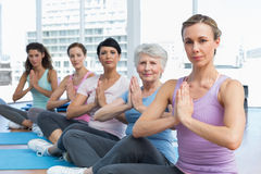 Class sitting with joined hands in a row at yoga class Stock Image