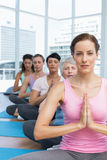 Class sitting with joined hands in a row at yoga class Stock Photo