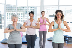 Class standing in namaste pose at yoga class Royalty Free Stock Image
