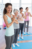 Class standing in namaste pose at yoga class Royalty Free Stock Photos