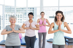 Class standing in namaste pose at yoga class Royalty Free Stock Images