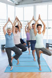 Class standing in tree pose at yoga class Stock Photo