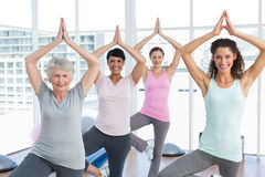 Class standing in tree pose at yoga class Royalty Free Stock Image