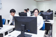 A class of students in front of their screens study computer science. Stock Photography