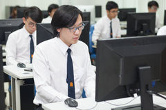 A class of students in front of their screens study computer science. Stock Photo