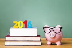 Class of 2016 theme with textbooks and piggy bank with glasses Royalty Free Stock Photo