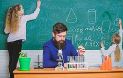 During class time. Teacher and little pupils in laboratory class. Bearded man teaching chemistry class. Small school stock photo