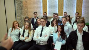 A class on a university listening a teacher. Group of students in a classroom, listening as their teacher holds a. Students with teacher in classroom. Caucasian stock footage