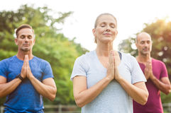 Class of yoga meditating. Three people at park meditating with joined hands and closed eyes. Senior women and mature men doing breath exercise outdoor. Group of Royalty Free Stock Photos